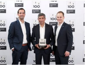 Physicist Dr. Ranga Yogeshwar presents the 2018 Innovator Award to Stefan Becker, Project Controller (left) and Dr. Alexander Hof, CEO, of HOF Sonderanlagenbau (right).